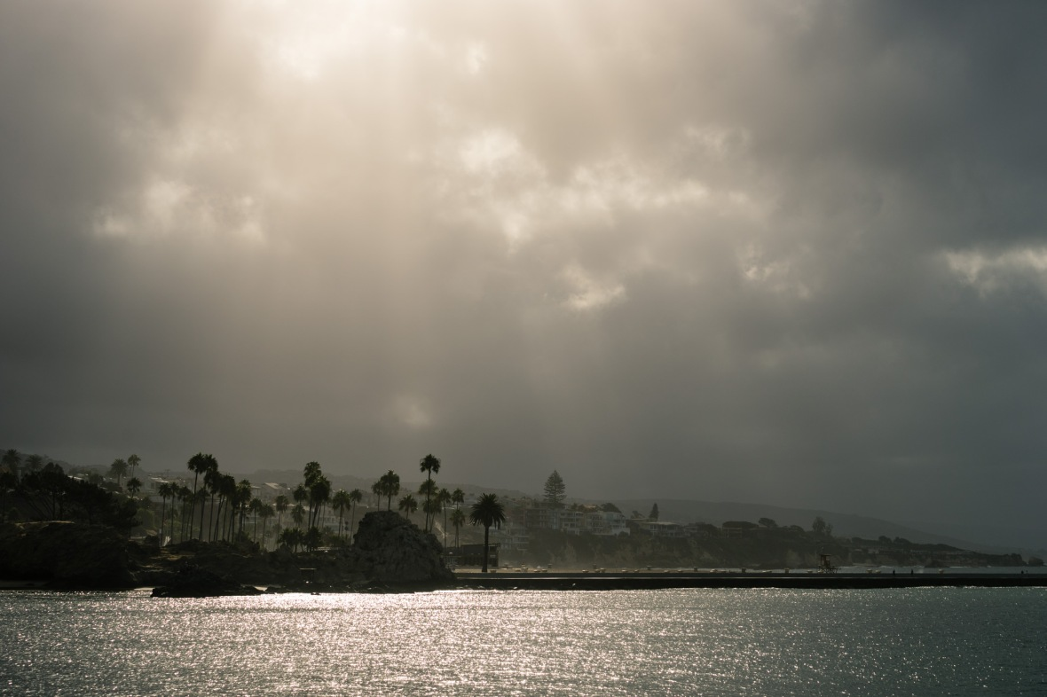 Picture of sunrays breaking through over the Wedge from Balboa Peninsula, Newport Beach, California, USA.