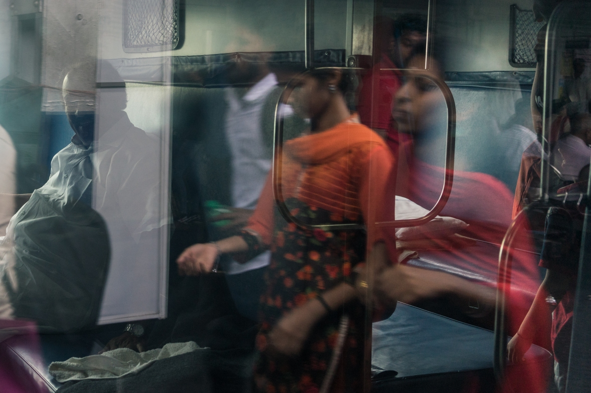 Travel and street photography of reflection in train window in Cochin, Kerala, India taken while Walking the Lanes by Mary Catherine Messner mcmessner